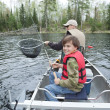 Stock Photo: Young fishermin canoe smiles seeing walleye netted