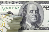 Stack of one hundred dollar bills with a large bill in the backg — Stock Photo
