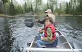 A young fisherman in a canoe smiles seeing walleye netted — Stock Photo