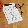 Basketball with coach's clipboard and whistle on wooden floor — Stock Photo
