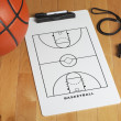 A basketball with coach's clipboard and whistle on a wooden gymn — Stock Photo