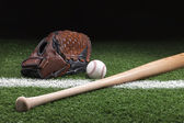 Baseball with mitt and bat on green grass at night — Stock Photo