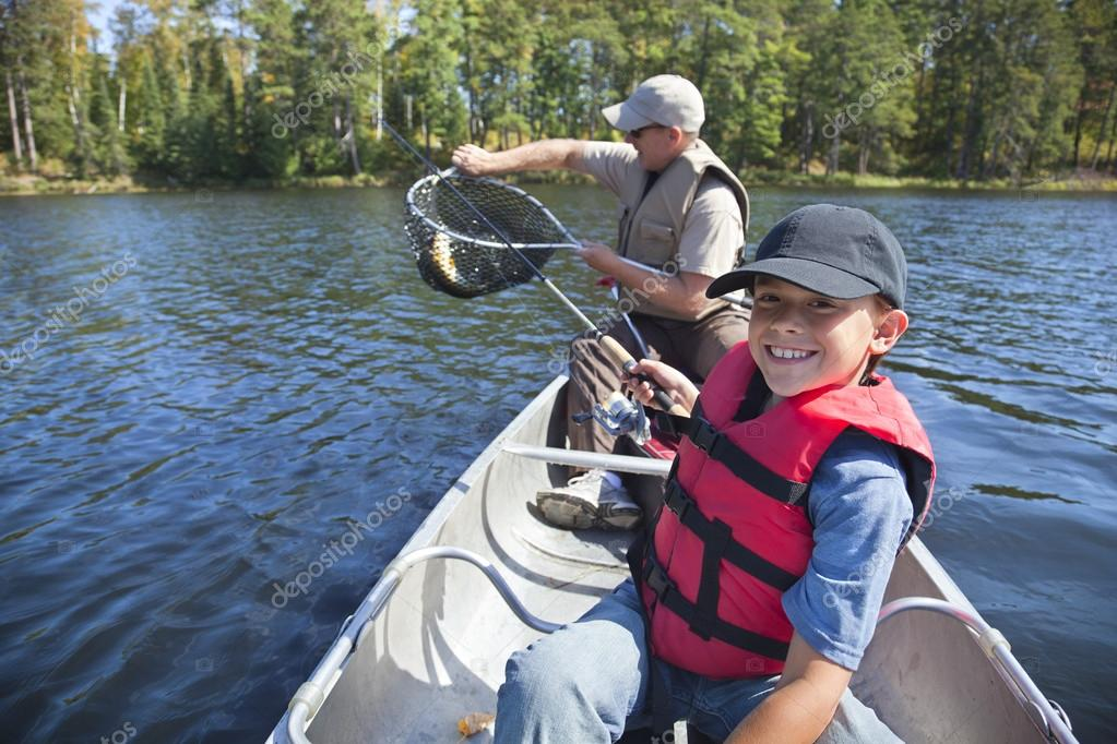 Young boy fisherman smiles at catch of nice walleye for Michigan fishing license prices
