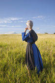 Amish woman standing in grassy field with afternoon sunlight — Stock Photo
