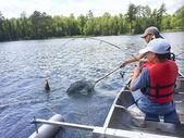 Boys fishing in a canoe catch a walleye — Stock Photo