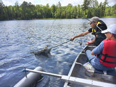 Boys fishing in a canoe catch a walleye — Stock Photo