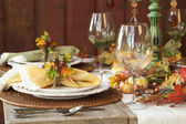 Fall dining place settings on rustic table and wall — Stock Photo
