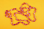 Pink necklace on yellow — Stock Photo