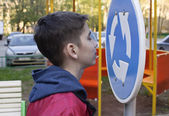 Teen looks at the road sign — Stok fotoğraf