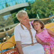 Little girl on bench with Grandma. — Stock Photo #15838025