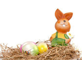Colorful easter eggs and rabbit on straw — Stock Photo