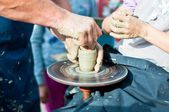 Hands working on pottery wheel — Стоковое фото