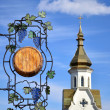 Wooden signboard with forged elements on а church background - Stock Photo