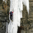 An Ice Climber going up a frozen waterfall. — Stock Photo