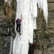 An Ice Climber going up a frozen waterfall. - Stock Photo