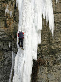 An Ice Climber going up a frozen waterfall. — Photo