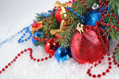 Christmas balls and garland on a spruce branch — Stock Photo
