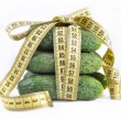 Cucumbers with yellow measuring tape — Stock Photo