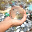 Globe in hands on garbage background. — Stock Photo