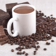 White cup of hot chocolate on coffee beans and chocolate backgro — Stock Photo