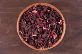 Dried petals of hibiscus in a wooden bowl — Stock Photo