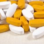 Heap of white and yellow pills — Stock Photo #44146975
