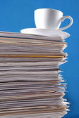 Cup on a pile of papers — Foto Stock