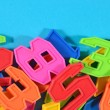 Heap of plastic colored numbers on a blue background — Stock Photo #51217009