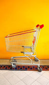 Empty shopping cart on yellow background. Side view — Stock Photo