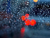 Defocussed traffic viewed through a car windscreen covered in rain, focus on raindrops — Stock Photo