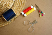 Sewing tools scissors, bobbins with thread and needles on wooden background — 图库照片