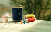 Old style image of cotton reels and other sewing items on a wooden table — Stock Photo