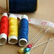 Sewing items: buttons, colorful fabrics, scissors, measuring tape, thimble, spools of thread on sewing pattern — Stock Photo #44752951
