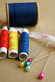 Sewing items: buttons, colorful fabrics, scissors, measuring tape, thimble, spools of thread on sewing pattern — Stock Photo