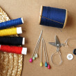Sewing items: buttons, colorful fabrics, scissors, measuring tape, thimble, spools of thread on sewing pattern — Stock Photo #44819781