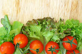 Tomatoes and lettuce on wooden background — Stock Photo