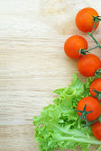 Fresh lettuces salad with tomatoes on wooden background — Stock Photo