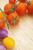 Branch of red ripe cherry tomatoes on a wooden board — Stock Photo