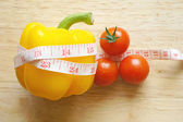 Yellow pepper bell wrapping with measuring tape and tomatoes (diet concept) — Stock Photo