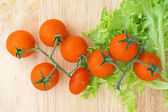 Fresh lettuces with tomatoes on wooden background — Stock Photo