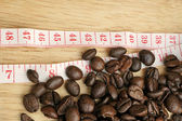 Coffee beans with measuring tape (diet concept) — Stock Photo