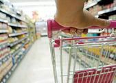 Closeup hand on shopping cart at supermarket — Stock Photo