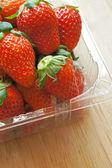 新鲜整个草莓在木质表面上的塑料包装纸盒 — 图库照片