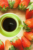 Coffee cup in strawberries frame — Stock Photo
