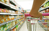 Closeup hand on shopping cart at supermarket — Stock Photo