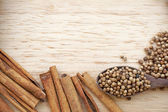 Spices scattered on wooden plate. Includes cinnamon, peppercorns — Stock Photo