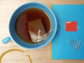 Primer plano de la bolsita de té y taza en la mesa de madera — Foto de Stock