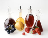 Four fruit vinegars — Stock Photo