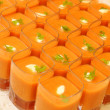 图库照片: Top view of orange candles lit in square glasses