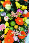 Colourful flower and fruit arrangement — Stock Photo